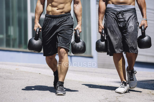 Cropped shot of two crossfit athletes doing exercise with kettlebells — Stock Photo