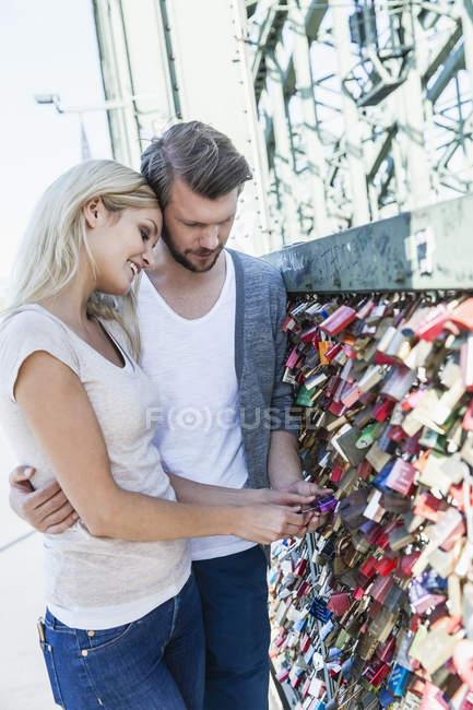 Germania, Colonia, giovane coppia che guarda le serrature d'amore sul ponte Hohenzollern — Foto stock