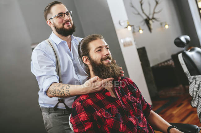 Man with full beard sitting in barbershop with barber — Stock Photo