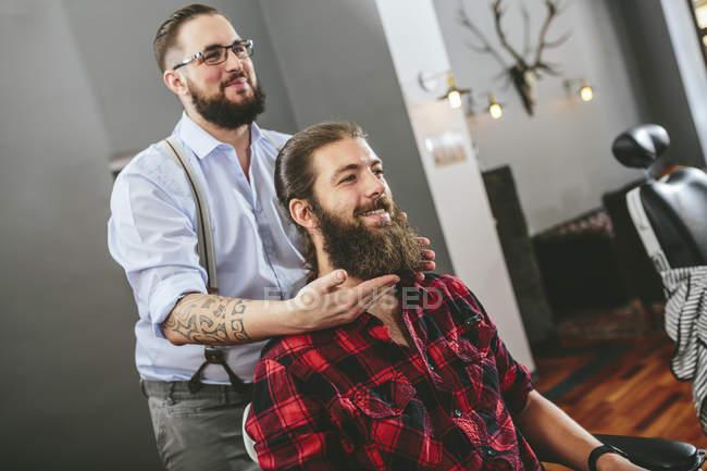 Homem com barba sentado na barbearia com barbeiro — Fotografia de Stock