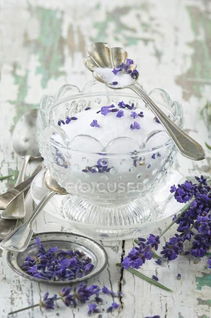 Sucre de lavande dans un bol en verre, lavande fraîche sur bois — Photo de stock
