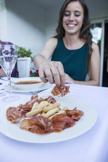 Жінка, взявши шматок іспанської шинки — стокове фото