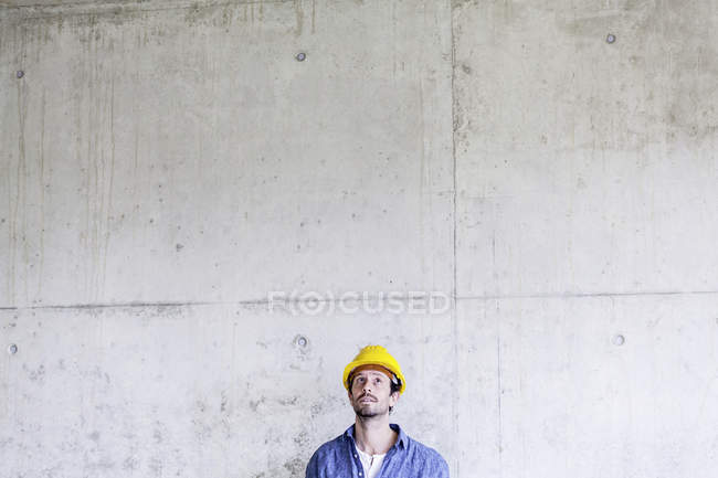 Man with hard hat on construction site at concrete wall looking up — Stock Photo