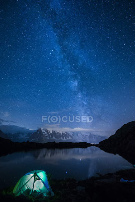 Scenic view of lit tent on shore of lake by night with Milky way and Mount Blanc reflected in lake, Lake Cheserys, Mont Blanc, France — Stock Photo