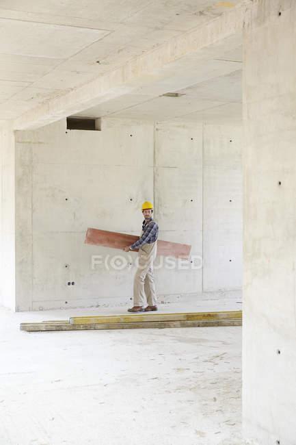 Працівник на будівельному майданчику, несучи дерев'яну шахівницю — стокове фото