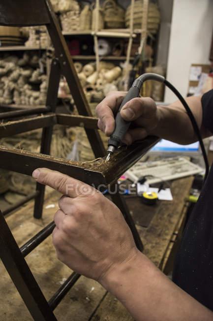 Homem limpando uma cadeira com uma lixadeira elétrica — Fotografia de Stock