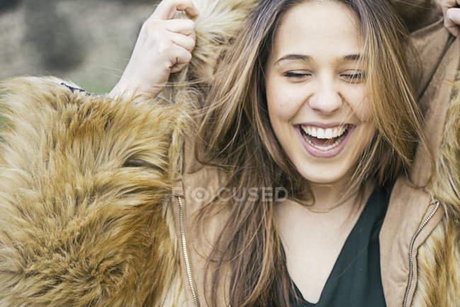 Портрет смеющейся женщины в меховой куртке — стоковое фото