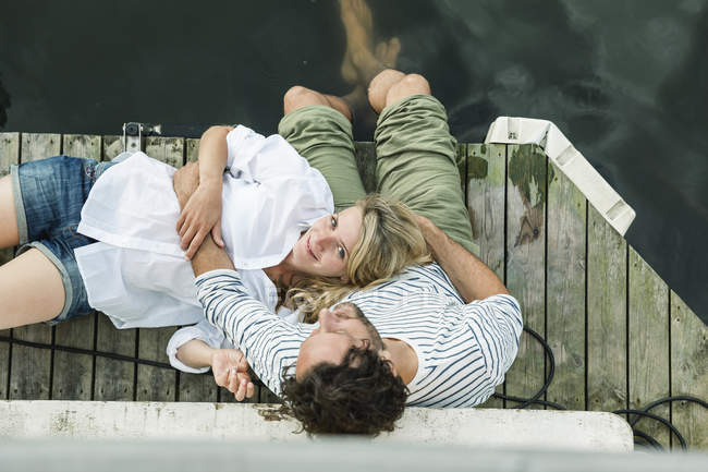 Smiling woman lying on man's lap at the water — Stock Photo