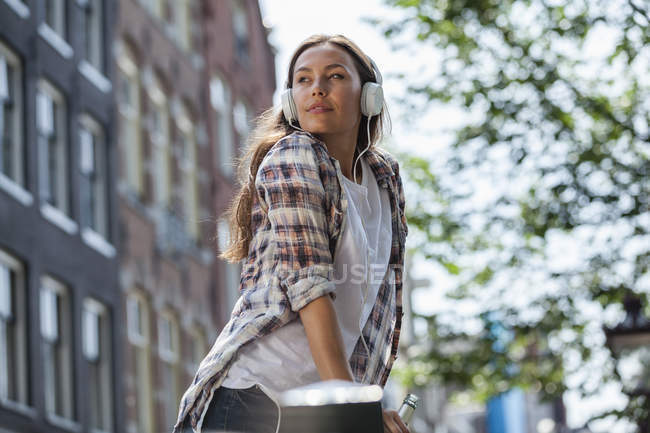 Netherlands, Amsterdam, young woman with headphones and beer bottle outdoors — Stock Photo