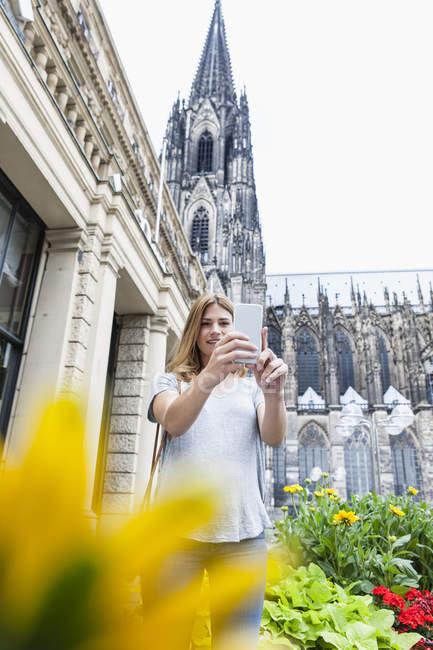 Alemania, Colonia, joven tomando una selfie con smartphone frente a la Catedral de Colonia - foto de stock