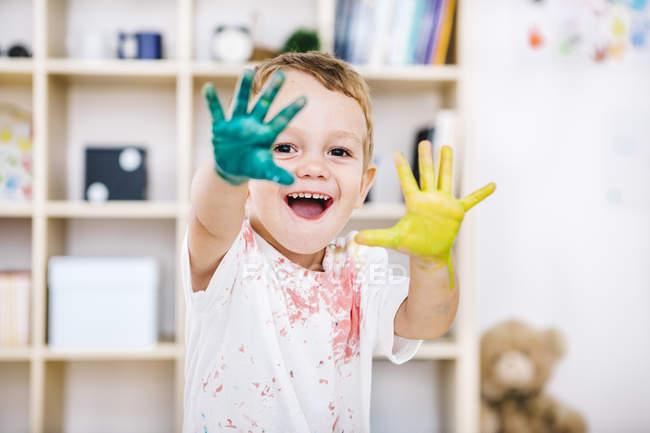 Портрет улыбающегося мальчика с раскрашенными руками — стоковое фото