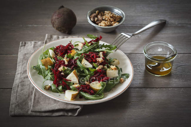 Plate of beetroot salad with rocket and walnuts on wooden surface — Stock Photo