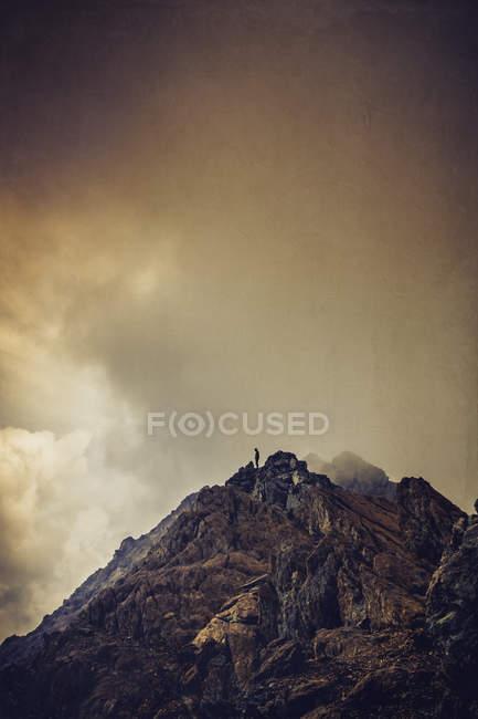 Силуэт человека на вершине горы, облака — стоковое фото