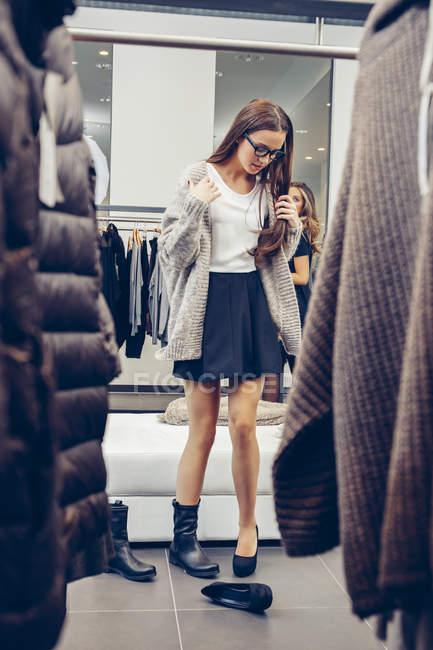 Молода жінка торговельна для взуття в бутік — стокове фото