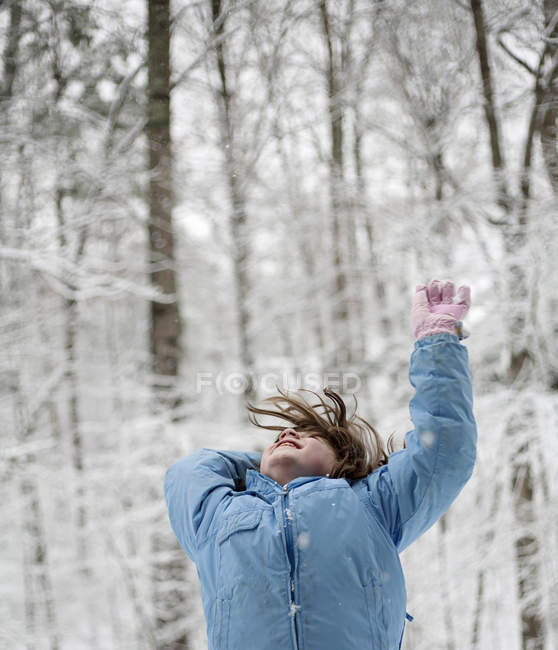 Happy little girl throwing snow in woods — Stock Photo