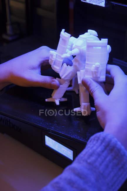 Primer plano de manos sosteniendo la estatuilla del robot 3d de impresora 3d - foto de stock