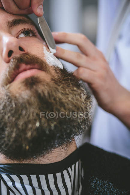 Close-up of Man with full beard getting a shave in barbershop — Stock Photo