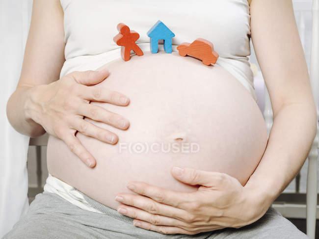 Беременная женщина перед детской кроваткой с игрушечным домиком, игрушечной фигуркой и игрушечной машиной на животе — стоковое фото