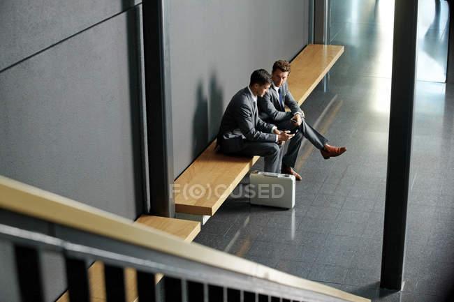 Deux jeunes hommes d'affaires assis sur le banc en utilisant un téléphone portable dans le hall du bureau — Photo de stock