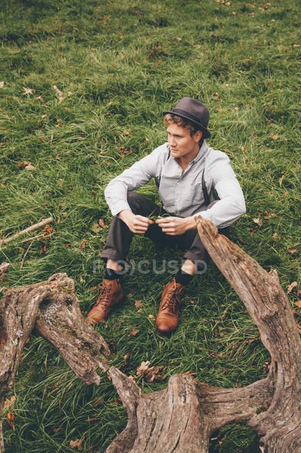 Young man wearing hat sitting on a meadow — Stock Photo