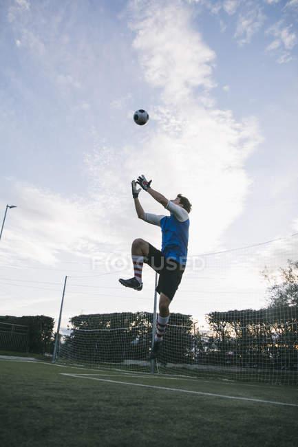 Вратарь пытается поймать футбол — стоковое фото