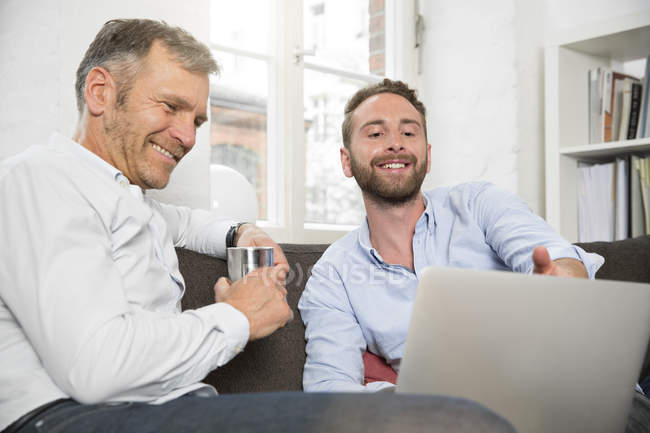 Two smiling businessmen sharing laptop — Stock Photo
