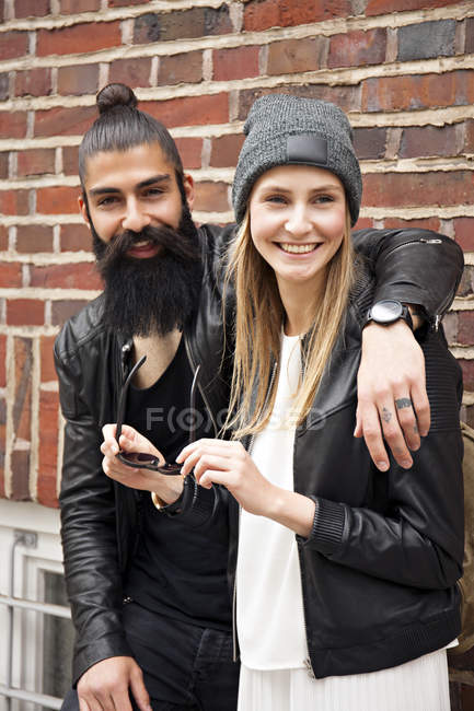 Portrait of happy young couple against brick wall — Stock Photo