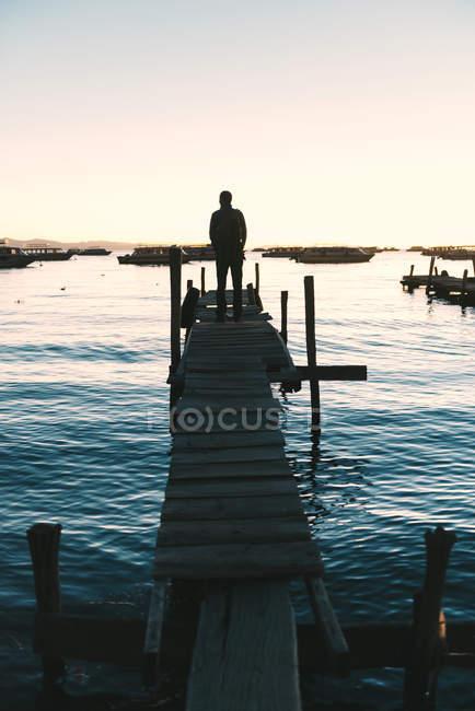 Bolívia, Homem em pé no calçadão de madeira com vista para o Lago Titicaca ao pôr do sol — Fotografia de Stock