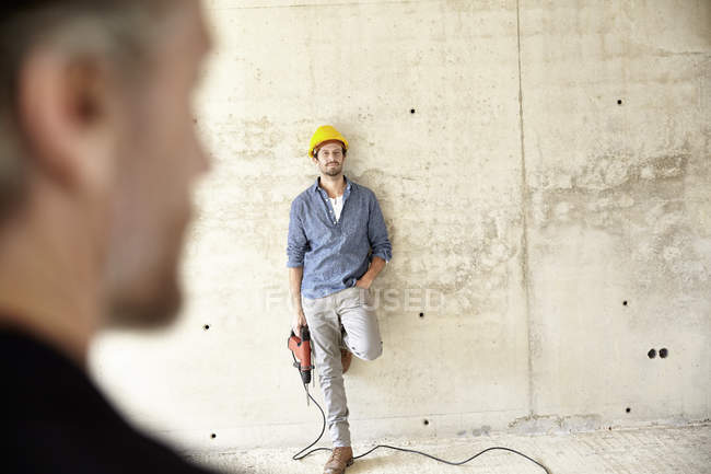 Man with hard hat site standing at concrete wall holding drill — Stock Photo