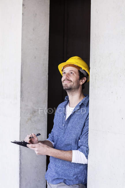 Man with hard hat on construction site looking up writing on clipboard — Stock Photo