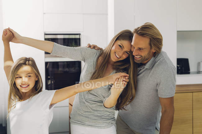 Happy father, mother and daughter at domestic kitchen — Stock Photo