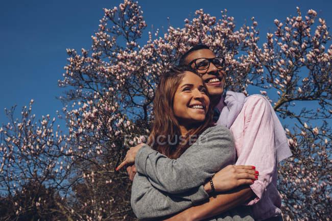 Щасливі молода пара, підтримуючи в парку — стокове фото