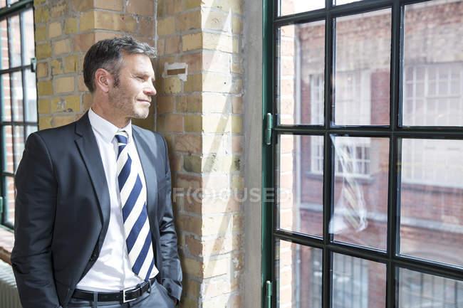 Mature businessman standing by window — Stock Photo