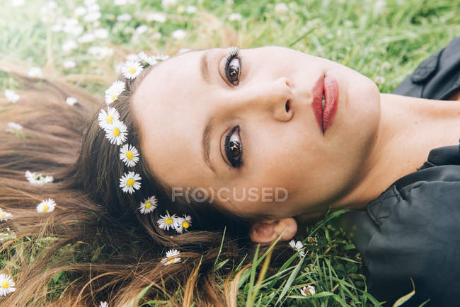 Portrait of young woman lying on grass with daisies in her hair — Stock Photo