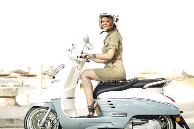 Mulher montando em scooter motor — Fotografia de Stock