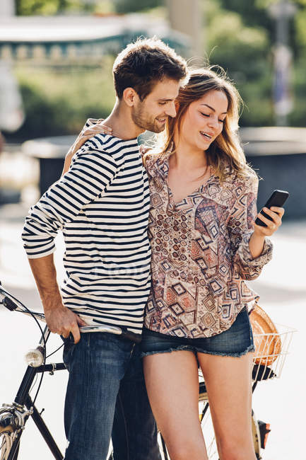Young lovers with bicycle standing on the street looking at smartphone — Stock Photo