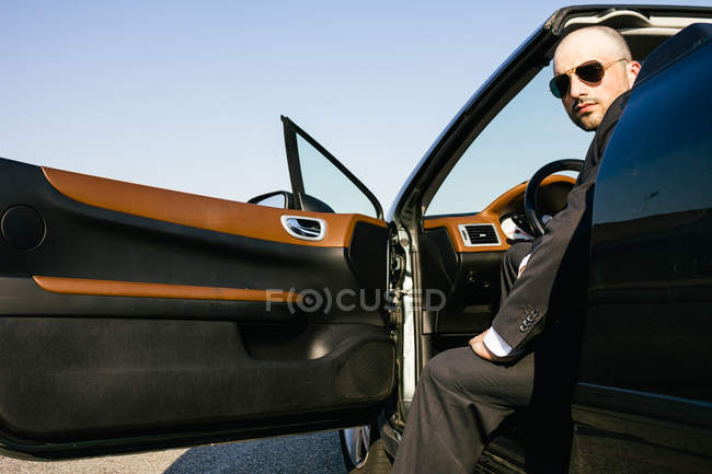 Portrait of businessman with sunglasses sitting on driver seat of a convertible car — Stock Photo