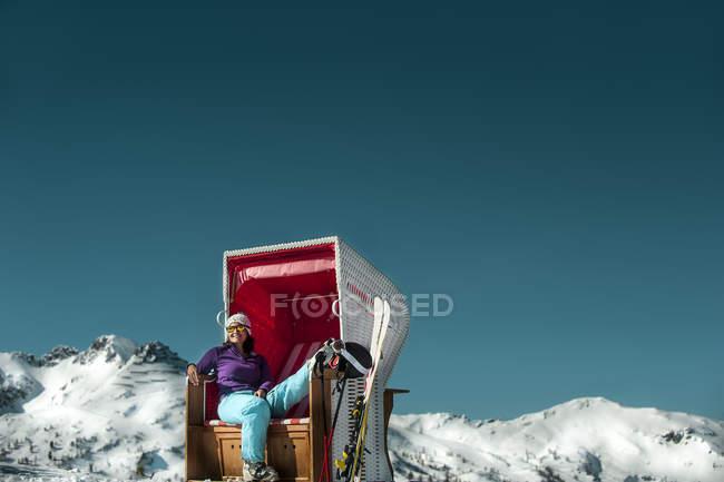Austria, Altenmarkt-Zauchensee, skier sitting in hooded beach chair in the mountains — Stock Photo