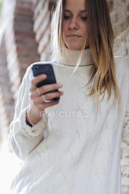 Ritratto di giovane donna che guarda il suo smartphone — Foto stock