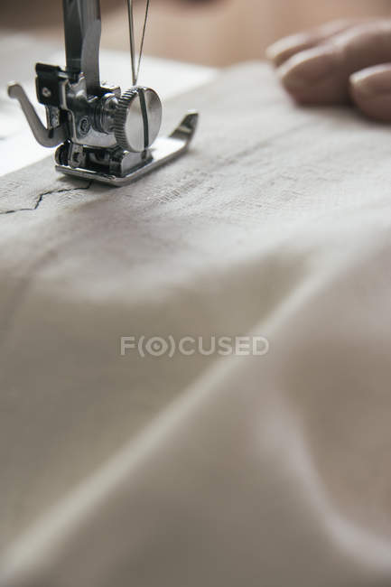 Sewing machine sewing on a white cloth — Stock Photo