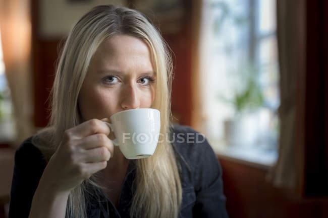 Retrato de mujer rubia bebiendo taza de café - foto de stock