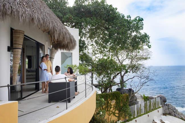 Amigos relaxantes no terraço da casa de férias à beira-mar — Fotografia de Stock