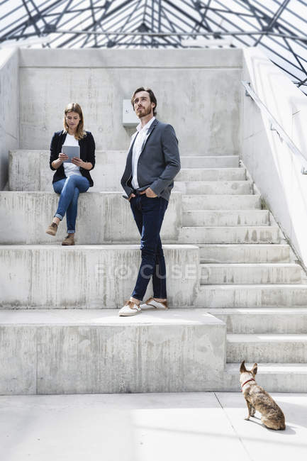 Two business people and a dog in modern architecture — Stock Photo