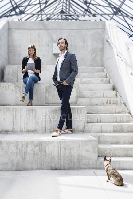 Deux hommes d'affaires et un chien dans l'architecture moderne — Photo de stock