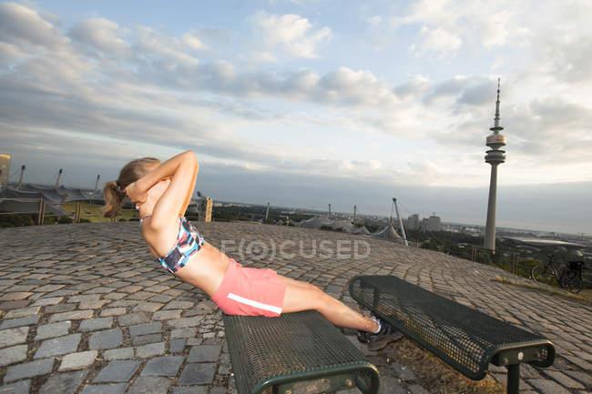 Mujer joven entrenando en una colina en la mañana - foto de stock