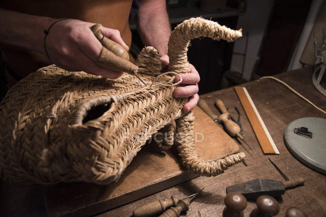 Artisan braiding a wicker bull's head in his workshop — Stock Photo