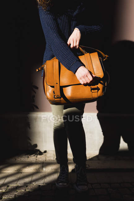 Woman carrying leather bag, partial view — Stock Photo