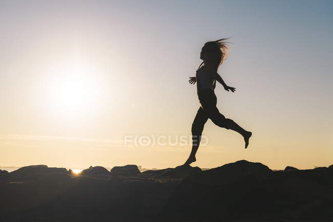 Silhouette of running woman at backlight — Stock Photo