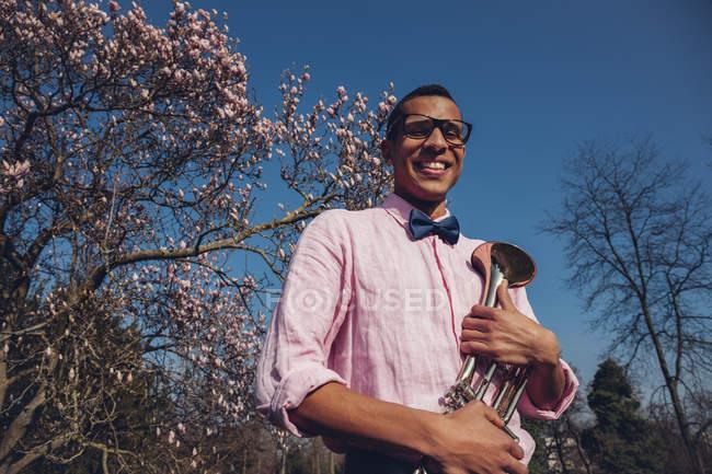 Jeune homme dans le parc au printemps, portant noeud papillon, tenant la trompette — Photo de stock