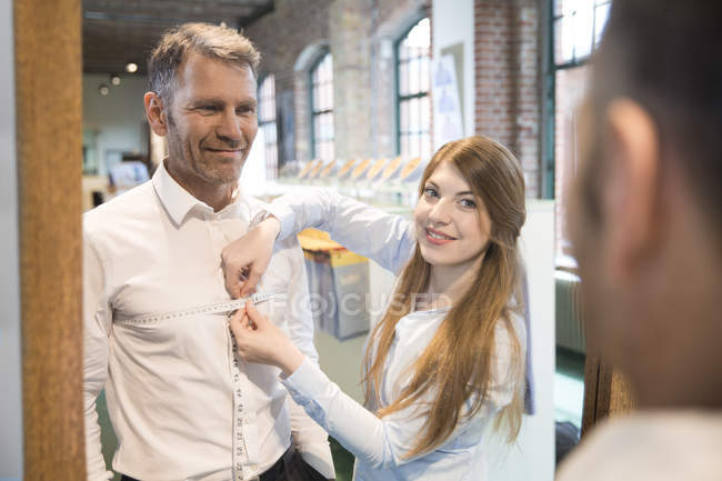 Seamstress taking chest measurement of client — Stock Photo